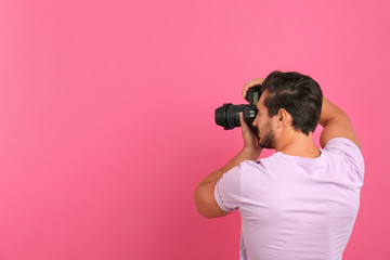 Young professional photographer taking picture on pink background. Space for text