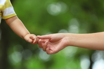 Mother with her baby holding hands together in park on summer day