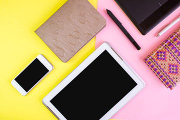 Flat lay of laptop, cell phone, earphones, digital gadget, modern concept on soft pink and yellow background with copy space