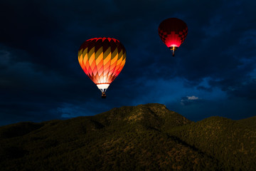 Poster Balloon Colorful glowing hot air balloons floating in a night sky over forested mountain peaks