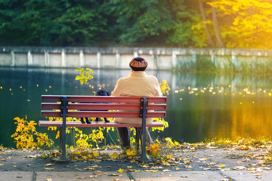 Lonely senior woman with a small black dog sitting on a bench by the autumn lake or river in a city park. Relaxation. Loneliness concept