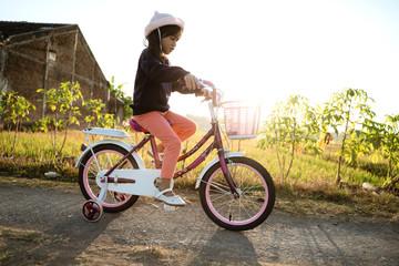 Fotobehang Fietsen toddler enjoy riding her bicycle outdoor in beautiful day
