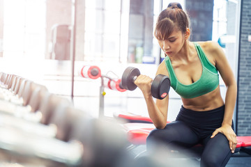 Sport woman workout with dumbbell at gym. Good health concept.