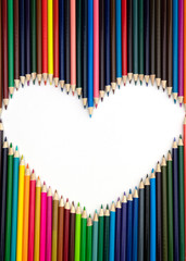 Colored pencils laid out on white background forming a white heart shape.