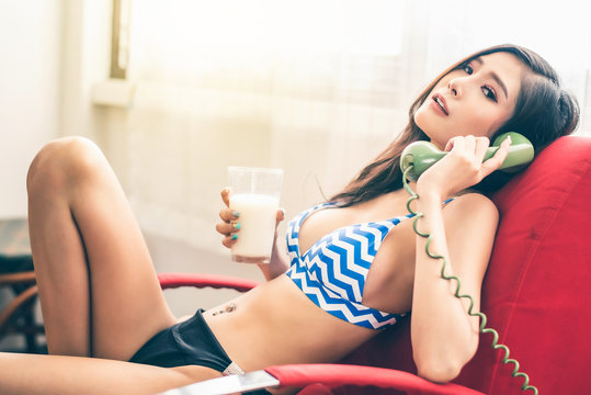 Beautiful attractive young Asian woman laying on sofa and using vintage telephone and hold milk glass in hand in the morning