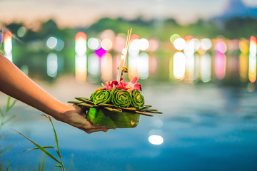A female tourist holds the Loy Krathong in her hands and is about to launch it into the water. Loy Krathong festival, People buy flowers and candle to light and float on water to celebrate the Loy Wall mural