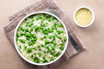Fresh homemade creamy green pea risotto in bowl, spoon and grated cheese on the side, photographed overhead