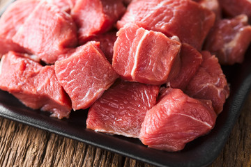 Fresh raw diced red beef meat on cast iron plate (Selective Focus)