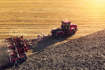 Agriculture machine harvesting crop in fields. Tractor pulls a mechanism for haymaking. Harvesting in autumn in the morning at dawn. agribusiness in the Altai region Russia. Wall mural