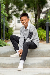 Portrait of a young Asian boy smiling outside.