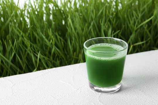 Glass of juice and fresh wheat grass on background. Space for text