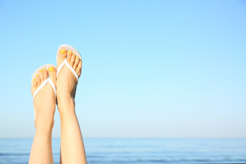 Closeup of woman wearing flip flops near sea, space for text. Beach accessories