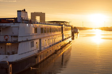 A ship in a canal during a golden sunrise in Holland. Groningen.