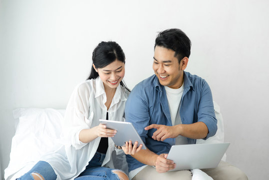 Surprising Asian couple using laptop at home, lifestyle concept.