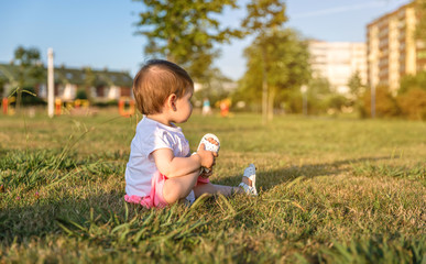 Adorable baby girl playing sitting on the grass park in a sunny summer day