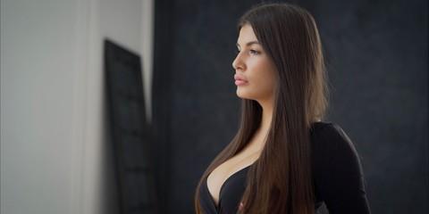 Sexy brunette flirts. beautiful and sexy brunette girl on dark background - portrait