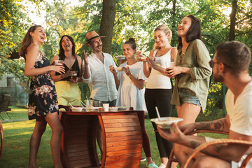Group of happy friends eating and drinking beers at barbecue dinner on sunset time. Having meal together outdoor in a forest glade. Celebrating and relaxing. Summer lifestyle, food, friendship concept Fototapete
