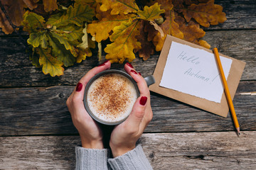 Autumn start composition still life. Woman's hands with cup of coffee, cappuccino, latter. autumn leaves, craft envelope and paper with text Hello Autumn on vintage background. Hot drink for autumn