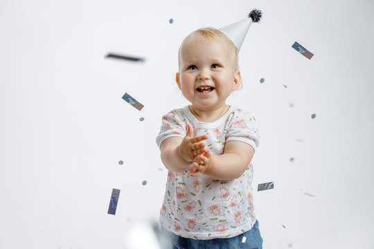 A little cute happy girl rejoices and laughs on her first birthday on a white background. Slapstick with confetti, a balloon filled with helium, a silver cap.