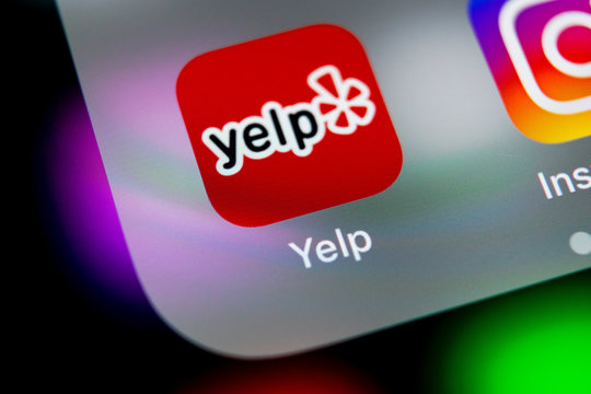 Sankt-Petersburg, Russia, August 16, 2018: Yelp application icon on Apple iPhone X screen close-up. Yelp app icon. Yelp.com application. Social network. Social media