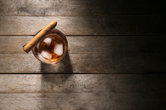 Glass of cold whiskey with cigar on wooden table