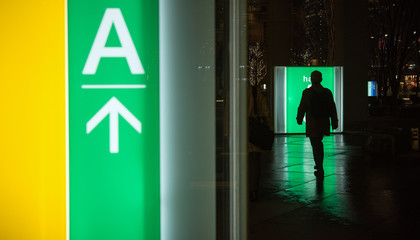 Commuter and illuminated directional signs in Tokyo at night