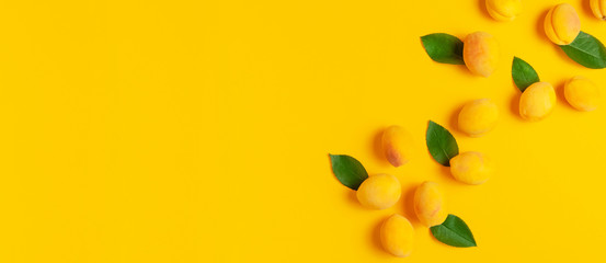 Wall Mural - Ripe fresh apricots fruits with green leaves on yellow background. Flat lay, top view, copy space. Fresh organic apricots, diet vegan food. Creative Apricot pattern. Harvest concept