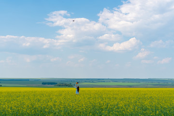 A happy girl with long hair is standing on the grass on a green field with a bright windmill in her hands. Dron takes a photo and video of a child in the field