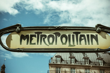 Paris, France - Aug 18, 2014: Art nouveau metropolitain sign in Paris, France ith traditional French real estate apartment building in the background