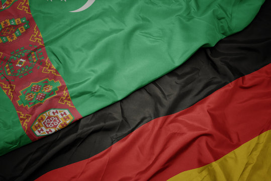 waving colorful flag of germany and national flag of turkmenistan.