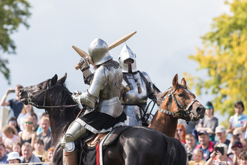 Two men knights riding horses on the battlefield and having a fight on wooden swords - people watching behind the fence