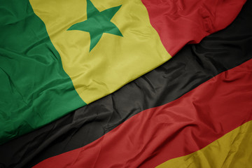 waving colorful flag of germany and national flag of senegal.