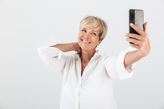 Image of joyous adult woman with short blond hair smiling and taking selfie photo on cellphone