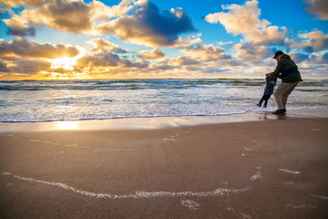 father and his little daughter playing with waves