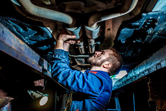 Handsome mechanic in uniform are working in auto service with lifted vehicle. Good Looking Mechanic Checking Out Vehicle. Mechanic examining under the car at the repair garage.