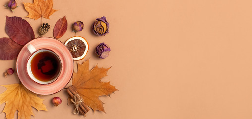 Wall Mural - Autumn Flat lay composition. Cup of tea, autumn dry bright leaves, roses flowers, orange circle, cones, decorative pomegranate, cinnamon sticks on brown beige background top view. Autumn, fall concept