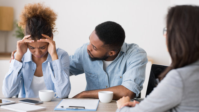 Black Husband Comforting Crying Wife On Finansial Counseling