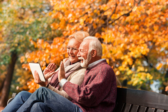 Happy senior couple talking with their grandkids via tablet in a