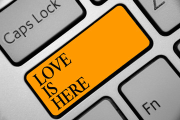 Conceptual hand writing showing Love Is Here. Business photo showcasing Romantic feeling Lovely emotion Positive Expression Care Joy Keyboard orange key computer computing reflection document
