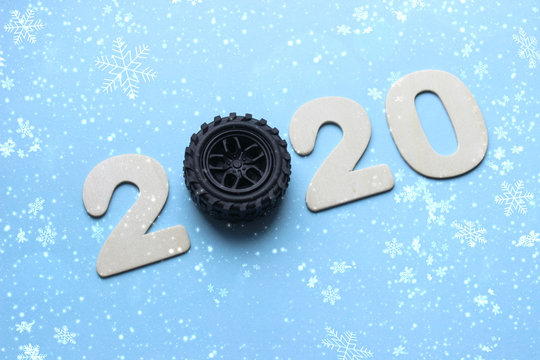 2020. The concept of the new year. The figures 2020 are isolated on a blue background, instead of the number 0 car wheel. New year background, copy space.