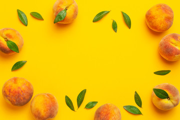 Wall Mural - Flat lay composition with peaches. Frame from ripe juicy peaches with green leaves on yellow background. Flat lay, top view, copy space. Fresh organic fruit, vegan food. Harvest concept