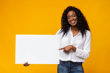 Afro girl is holding yellow advertising board Wall mural