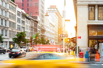New York City street scene with yellow taxi cab driving down 5th Avenue through Midtown Manhattan