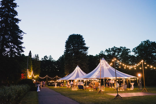 Coziness and style. Modern event design. Lounge zone and wedding reception decorations outdoors in the evening.