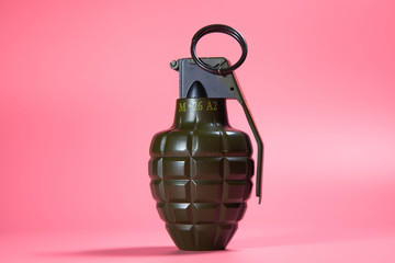 Green metal hand Grenade with round pin over When I pull out it will blow Bomb On a pink background