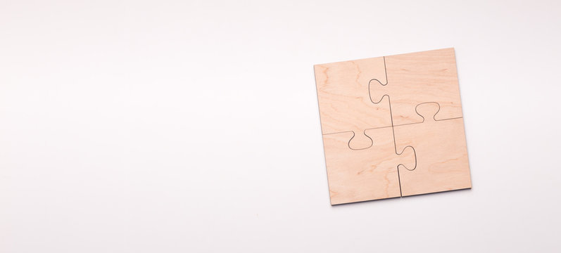 Puzzle of four wooden pieces with copy space for text