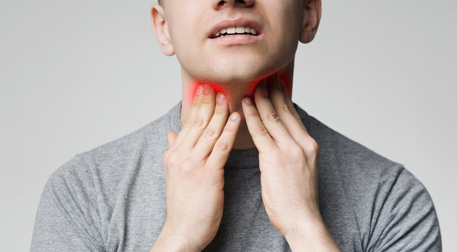 Young man pulping his inflamed neck, close up