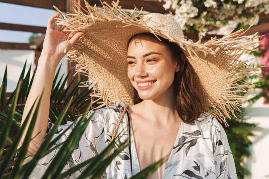 Positive happy young beautiful woman at the beach walking in a beautiful sunny morning over tropical plants.