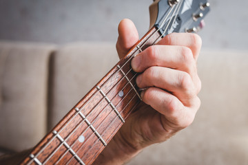 B7 chord - close-up male Caucasian hand takes a chord on a 6 string guitar