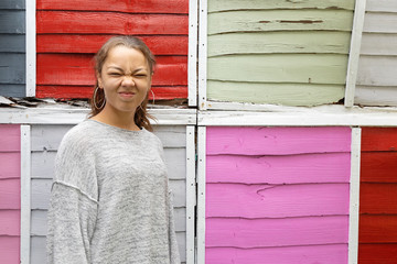 Portrait of a girl with colored fence behind. Frontal view. Nobody inside